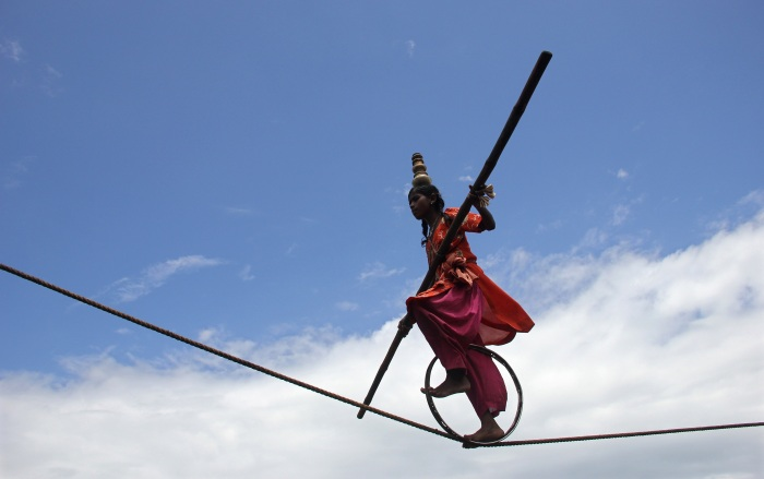 A tightrope walker performs on a rope while holding a balancing pole during a performance at Puri